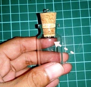 memasang bor kawat pada tutup botol