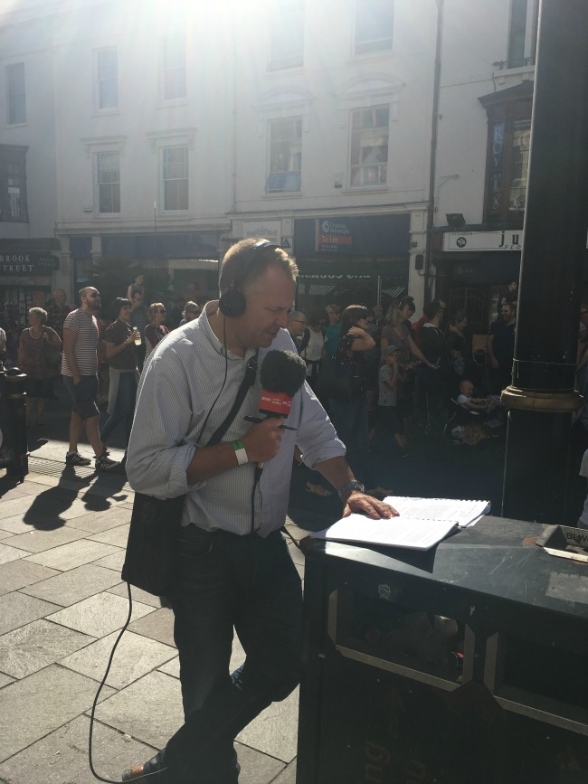 City-Of-The-Unexpected-Cardiff-Celebrates-Roald-Dahl-Jamie-Owen-presenter-reading-with-microphone-and-headphones