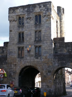 Cars pass through the Micklegate Bar, back side, York, England