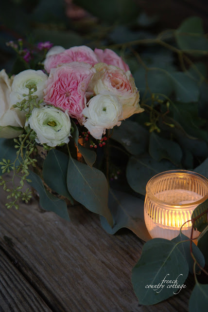 Candle and roses on table top with eucalyptus garland