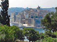 A view of Valletta from across the harbour. It looks like it is on an island.