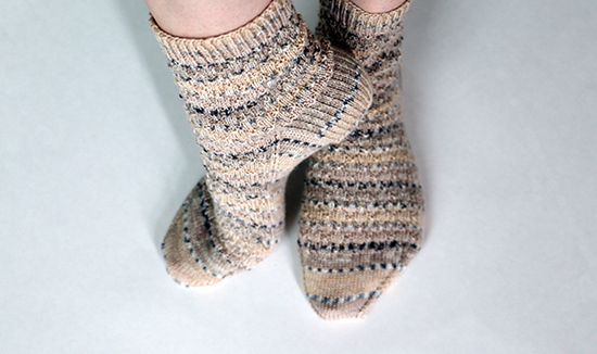 Relaxed Pose for Hand Knit Wool Socks in Beige and Gray Self-Striping Yarn