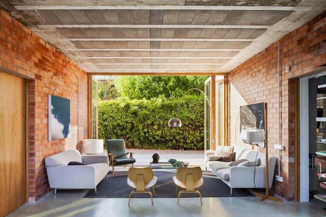 Let the outdoors in with these red brick walls, fold-away French doors and simple white couching.