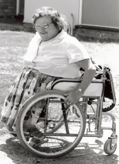 Black and white photo of my mum in her wheelchair outside what was our home at the time.