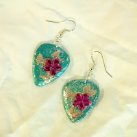 Metallic Blue guitar pick earrings with flower gems and butterflies.