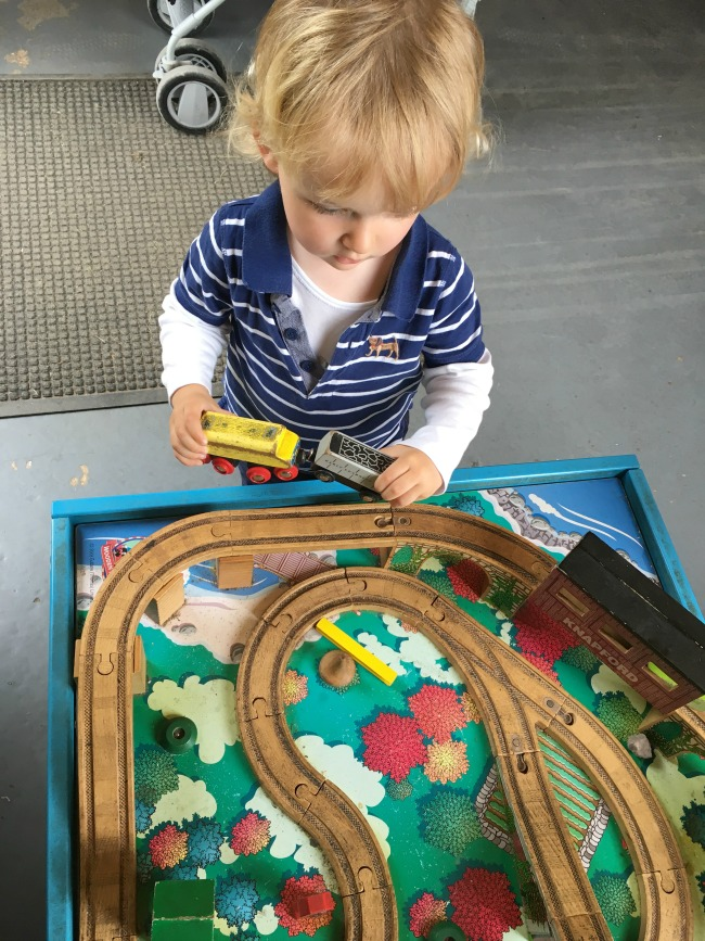 toddler-playing-with-wooden-train-set