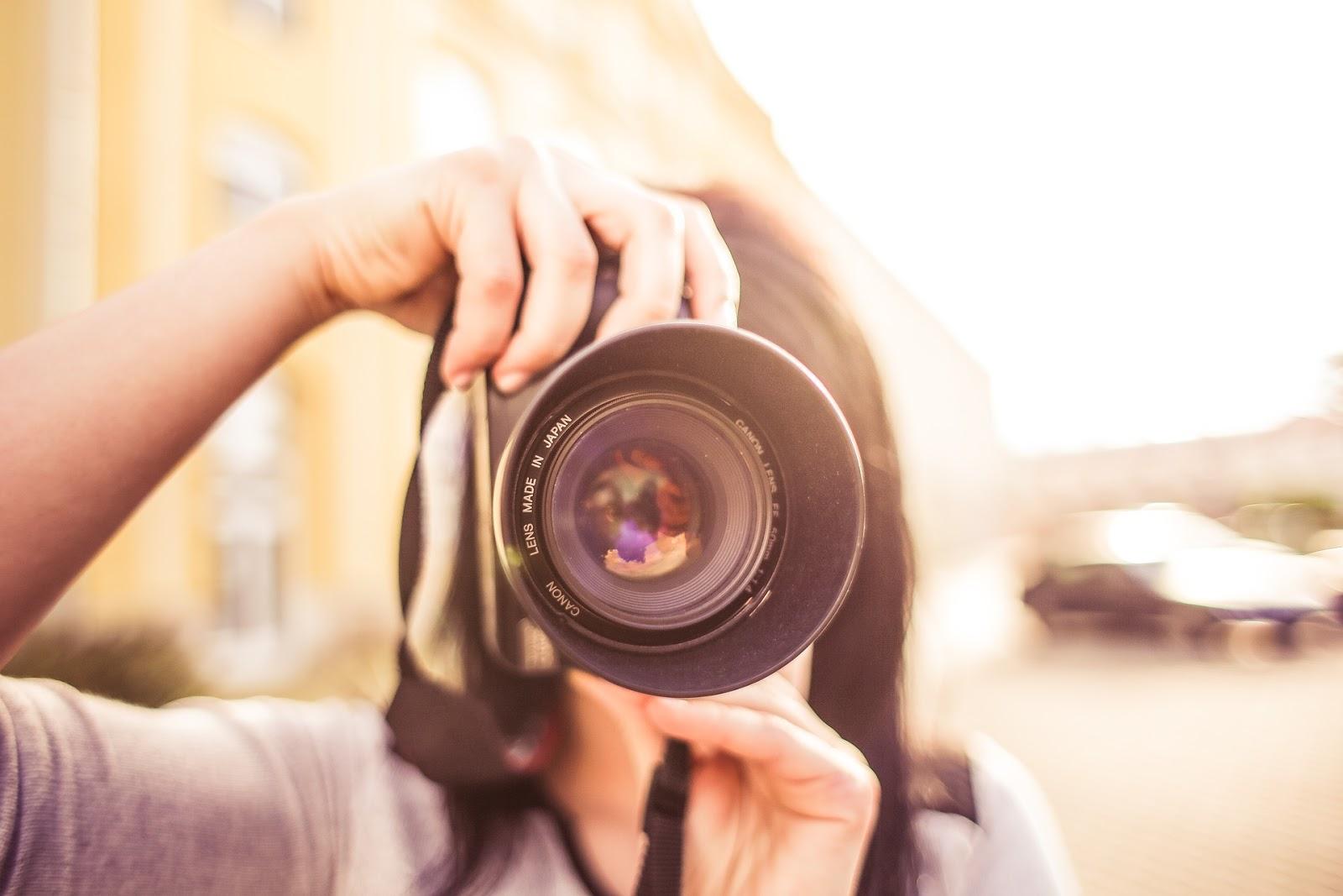 Девушка держит фотоаппарат