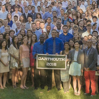 "A color photograph of a smiling crowd of people, two holding up a sign reading ""Dartmouth 2016."""
