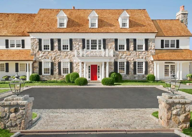 tradition stone exterior of a mansion with black shutters, columns and a red door
