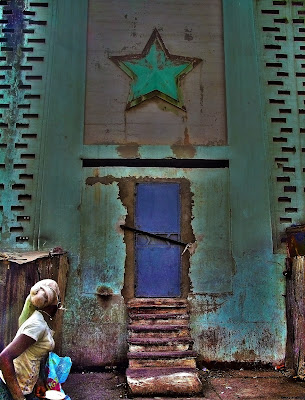 A woman stares at a boarded up door in Dakar, Senegal.