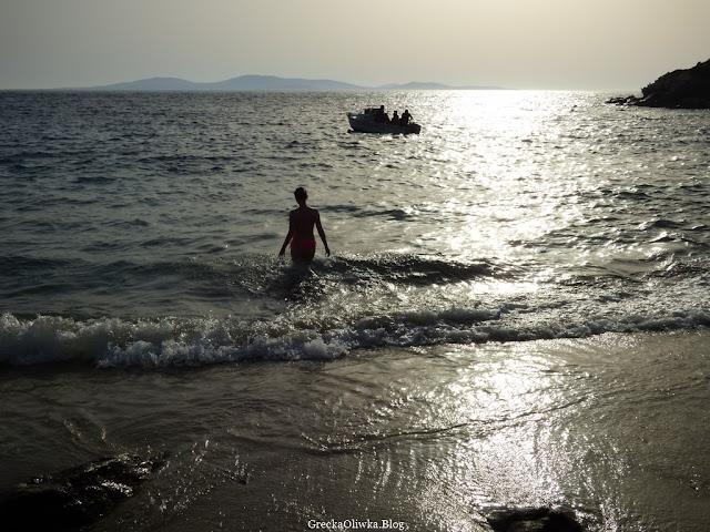 kobieta w stroju kąpielowym na tle srebrzyście mieniącego się greckiego morza w Zatoce Kapari w oddali łódka z pasażerami