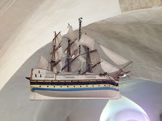a model of a three-masted sailing ship hangs from a whitewashed arch