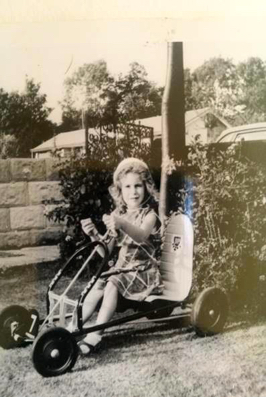 Photograph of The author Nikki Greenleaf in her kiddy car. Image courtesy of Nikki Greenleaf