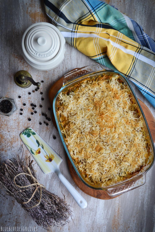 Vista cenital lasaña berenjenas en fuente de cristal sobre tabla de madera, bandeja porcelana con salero y pimentero, paño cocina de colores