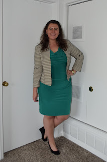 a woman wearing a green sheath dress, a black and white striped blazer, and black wedges