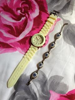 A cream watch and an evil eye bracelet