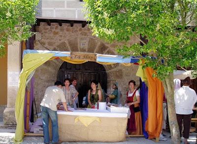 Puesto de rosquillas en mercado medieval con mujeres ataviadas a la antigua