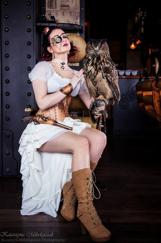 Steampunk woman holding owl and gun, wearing tan leather corset and boots, white blouse, white skirt, eyepatch and goggles, steampunk jewelry. Women's steampunk fashion and costumes