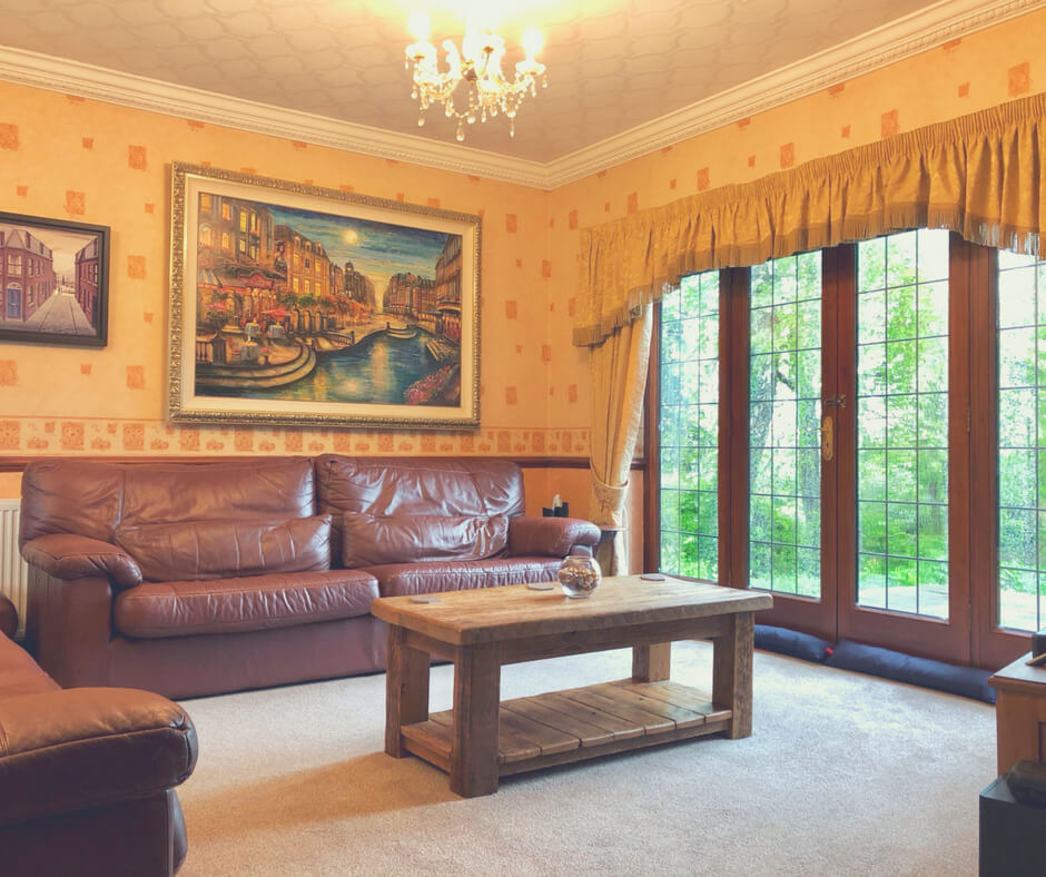 A tidy lounge with a brown leather sofa and wooden coffee table. An example of #mumwinning.