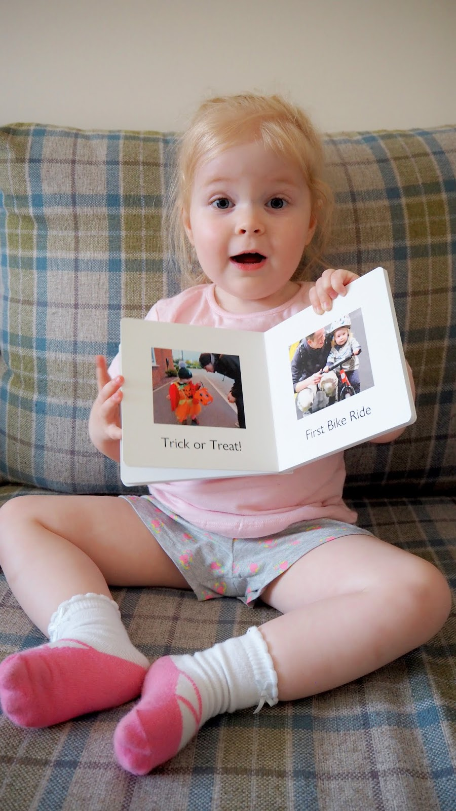 Elise holding the photo book up with an excited/shocked expression on her face. You can see a photo of her trick or treating and on a balance bike.