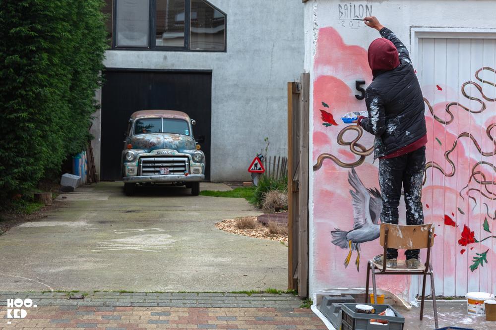 Brazilian street artist Mateus Bailon pictured at work on a mural in Ostend, Belgium