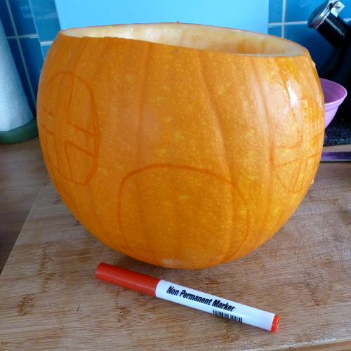 Drawing design onto a pumpkin before carving it for Halloween