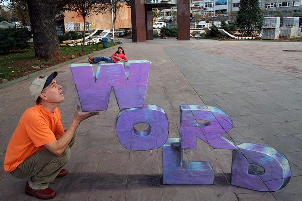 Kaldırımda yazılı olan mor renkli WORLD sözcüğü gösteren kaldırım sanatı resmi