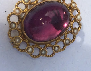 Purple cabochon brooch with reflection of two fingers.