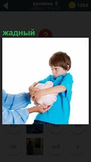 У жадного мальчика в руках копилка, которую он не хочет отдавать