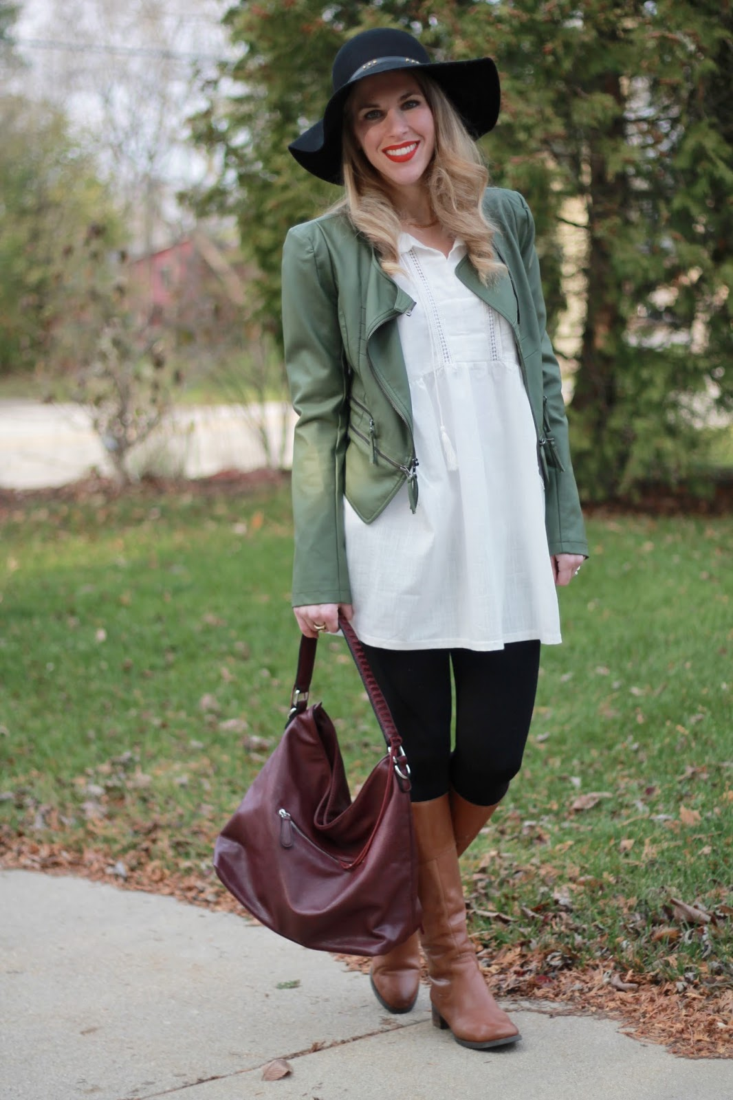 white tunic, black leggings, olive moto jacket, black floppy hat, cognac riding boots, burgundy bag