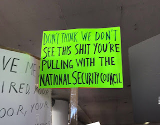 "A sign saying ""Don't think we don't see this shit you're pulling with the National Security Council"""