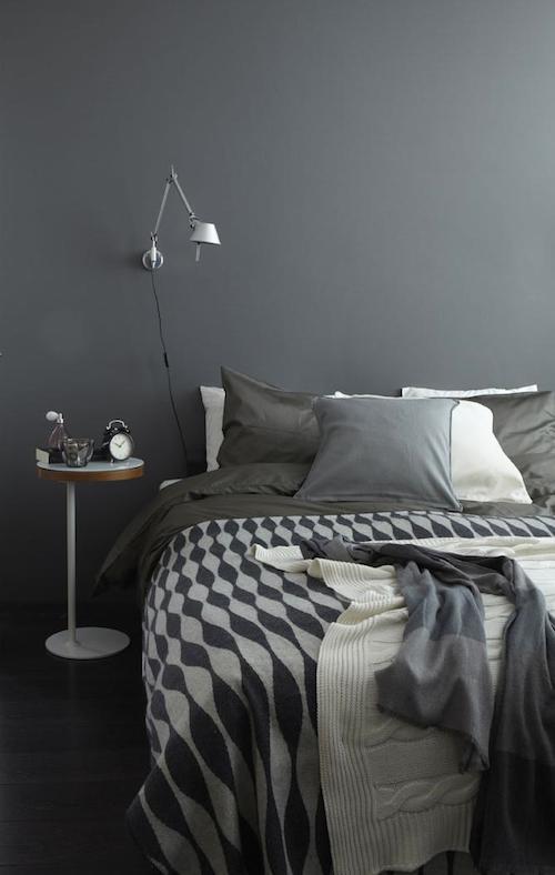 Graue Wandfarbe, Bett mit Kissen und Decken in Grautönen dekoriert, weißer Beistelltisch
