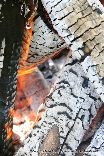 Viewing the inner core of the campfire, logs all coated in white ash, orange flames licking the wood.