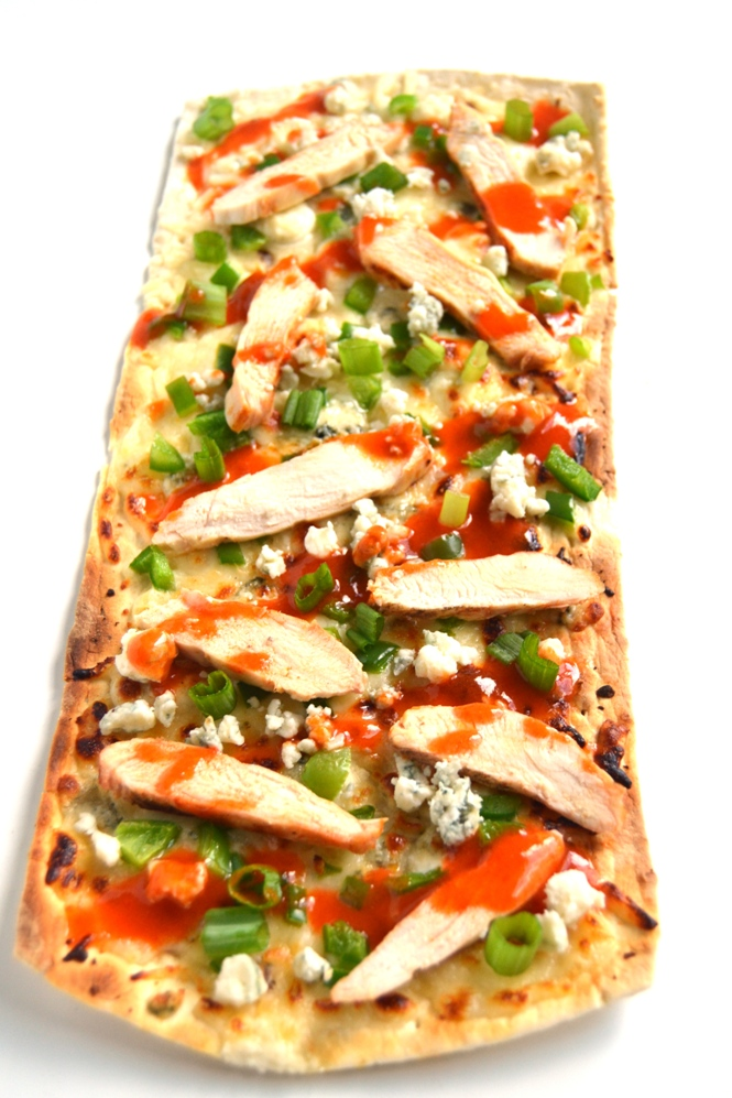 Buffalo Chicken Flatbread Pizza is easy to make and is full of flavor with spicy buffalo chicken, creamy blue cheese and flavorful green onions! www.nutritionistreviews.com