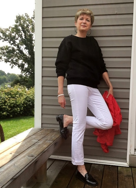 woman wearing white jeans, black sweatshirt, and black loafers, holding a red windbreaker