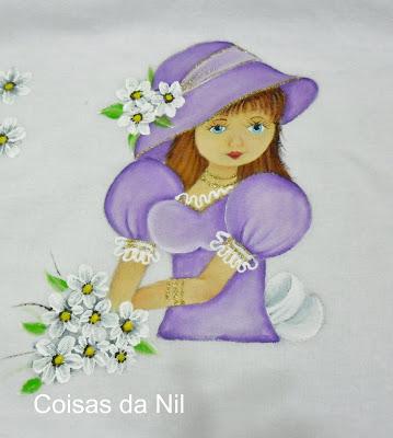 boneca pintada com chapeu lilas e flores para colocar saia de croche