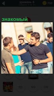 Встретились знакомые парни на улице и здороваются друг с другом