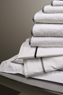 A clean stack of white towels with grey accents