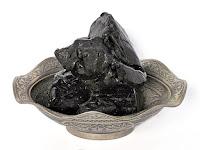 Gümüş işlemeli dalgalı bir tabak içindeki siyah renkli meyan balı