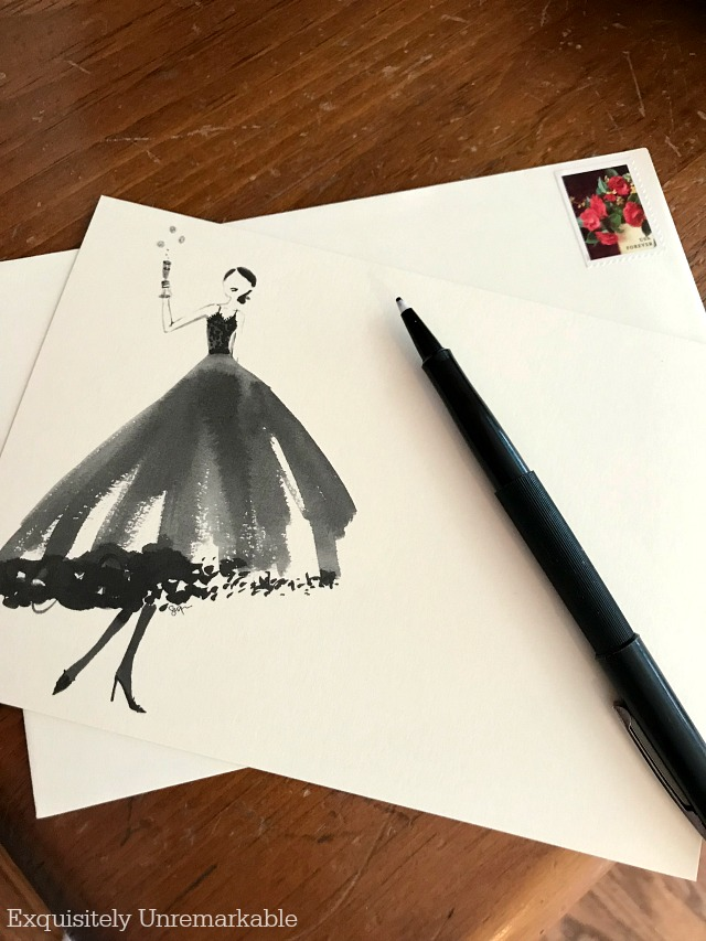Stationary with a drawing of woman in a dress, toasting, next to a pen and envelope