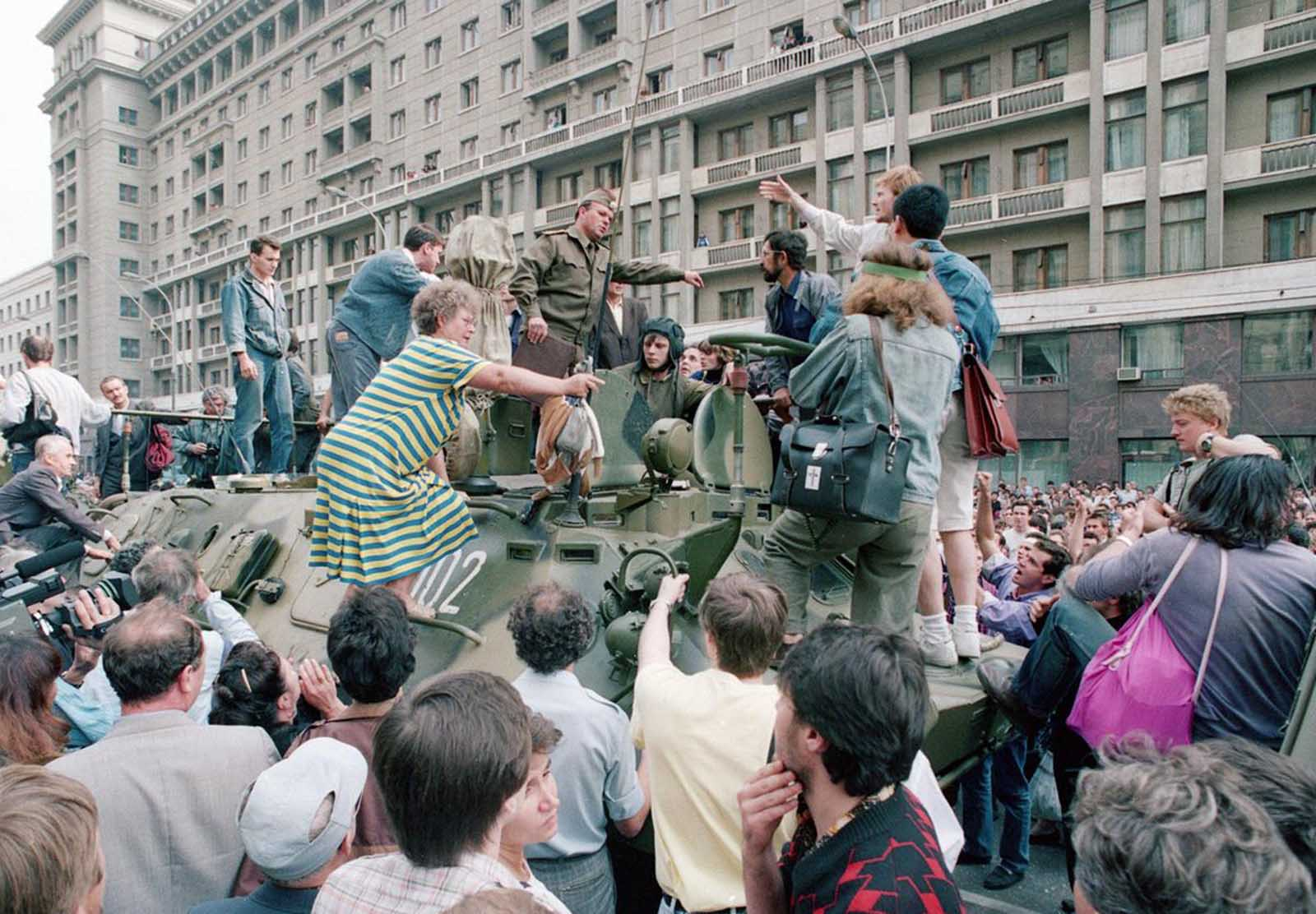 A crowd gathers around a personnel carrier as some people climb aboard the vehicle and try to block its advance near Red Square in downtown Moscow, on August 19, 1991. Military vehicles were on the streets of Moscow following the announcement that Soviet President Mikhail Gorbachev was replaced by Gennady I. Yanayev in a coup attempt by hard-line Communists.