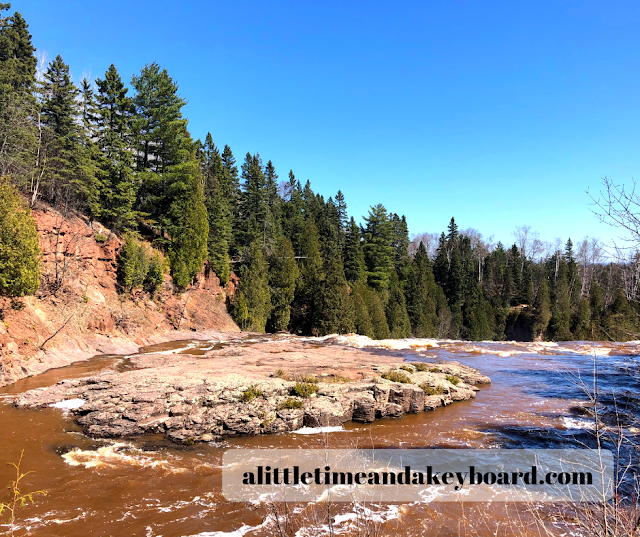 Rolling rapids surrounded by verdant evergreens at Gooseberry Falls State Park in Minnesota.