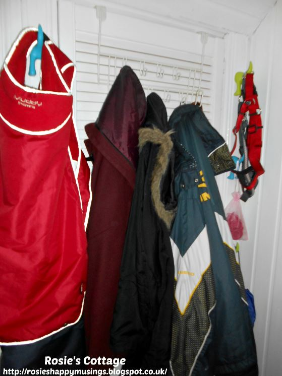 Coats hanging in the newly painted entryway/mudroom