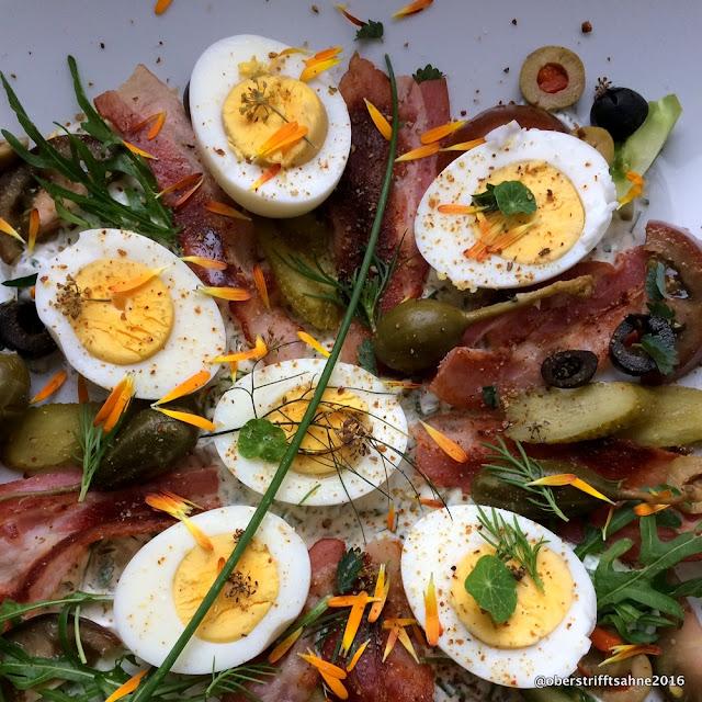 Eiersalat mit Oliven, gebratenem Frühstücksspeck, vielen Kräutern, Kapernäpfeln, Ruccola und Kräutersahne