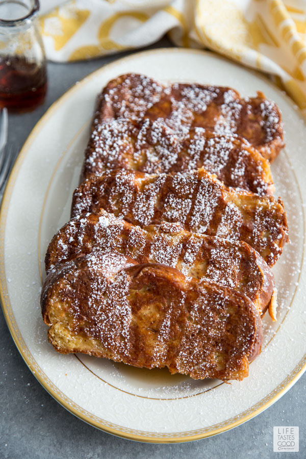 Oven French Toast topped with powdered sugar and syrup on a white serving plate