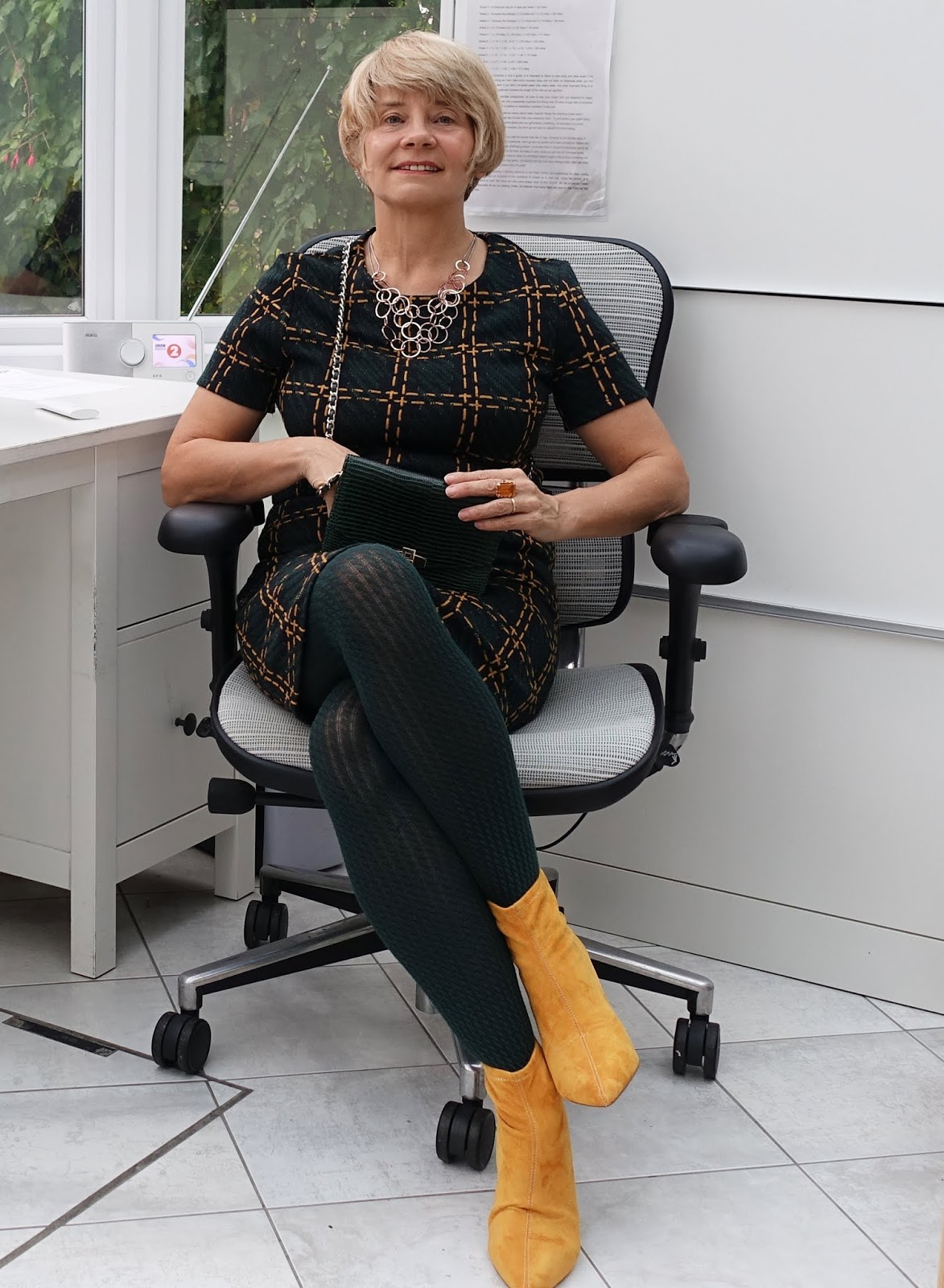 Over-45s style blogger Gail Hanlon in forest green and mustard stripe dress from Sainsbury's, mustard pull-on ankle boots, also Sainsbury's, and green ribbed tights