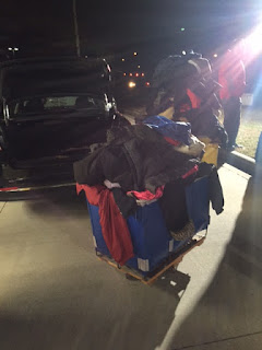 Generously donated coats piling up in a blue A Cleaner World bin