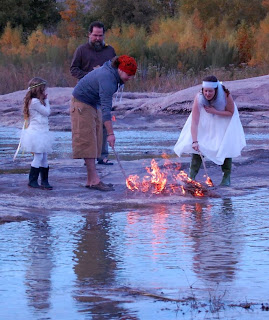 man and woman lighting a fire by a river