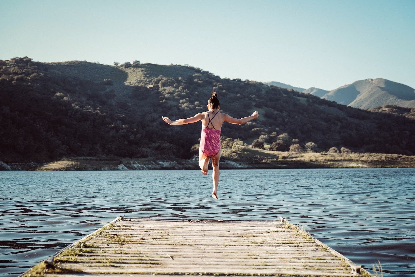 Young girl jumping into a loch