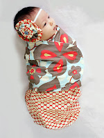 Çiçek desenli kundağa sarılmış bir bebek